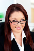Bright businesswoman holding her glasses sitting in her office — Stock Photo
