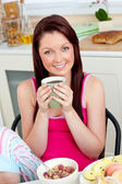 Charming woman eating her breakfast at home holding a cup of cof — Stock Photo