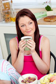 Cute woman eating her breakfast at home holding a cup of coffee — Stock Photo