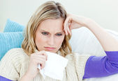 Diseased woman lying on a sofa with tissues — Stock Photo