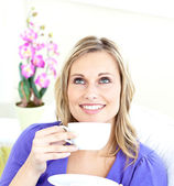 Delighted young woman holding a cup of coffee on a sofa — Stock Photo