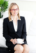 Delighted businesswoman wearing glasses drinking coffee sitting — Stock Photo