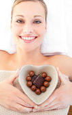 Cheerful woman holding a bowl in the shape of a heart with choco — Stock Photo