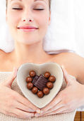Bright woman holding a bowl in the shape of a heart with chocola — Stock Photo