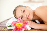 Close-up of a delighted woman lying on a massage table with a fl — Stock Photo