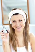 Smiling woman holding an eyelash curler looking at the camera in — Stock Photo