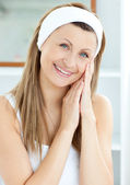 Smiling young woman putting cream on her face in the bathroom — Stock Photo