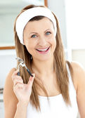 Cheerful woman holding an eyelash curler looking at the camera i — Stock Photo