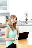 微笑手机在厨房中使用笔记本电脑上的女人 — 图库照片
