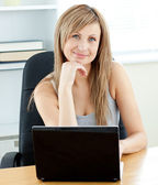 Charismatic young businesswoman using her laptop sitting at her — Stock Photo