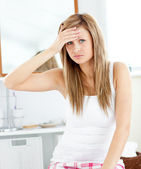 Depressed woman with a headache looking at the camera in the bat — Stock Photo