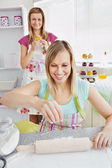 Smiling female friends baking pastry in the kitchen — Stock Photo