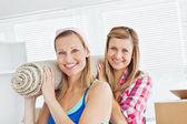 Two cute women carrying a carpet at home — Stock Photo