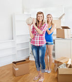 Two bright women carrying a carpet at home — Stock Photo