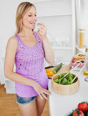Delighted woman eating cucumber in the kitchen — Stock Photo