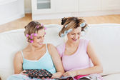 Close female friends with hair rollers eating chocolate reading — Stock Photo