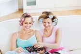 Amigos femininos positivos com rolos de cabelo comendo chocolate readi — Fotografia Stock
