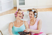 Laughing female friends with hair rollers eating chocolate at ho — Stock Photo