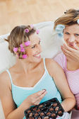 Beautiful female friends with hair rollers eating chocolate at h — Stock Photo