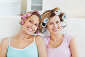 Laughing female friends with hair rollers on a sofa — Stock Photo