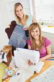 Bright young female friends sewing clothes together at home — Stock Photo