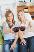 Two bright women holding a wineglass on a sofa — Stock Photo
