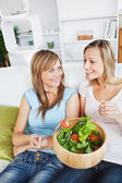 Two female friends eating salad together on a sofa — Stock Photo