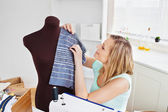 Delighted young woman sewing clothes at home — Stock Photo