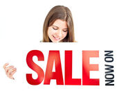 "Attractive woman holding a card where ""SALE"" is written — Stock Photo"