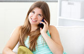 Beautiful woman talking on phone sitting on a sofa — Stock Photo