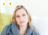 Exhausted woman lying on the sofa with a grey pullover — Stock Photo