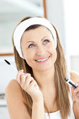 Jolly young woman using mascara in the bathroom — Stock Photo