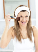 Smiling caucasian woman putting powder on her face smiling at th — Stock Photo
