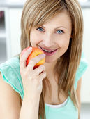 Captivating caucasian woman eating an apple in the kitchen — Stock Photo