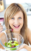 Jolly woman eating a fruit salad smiling at the camera in the ki — Stock Photo