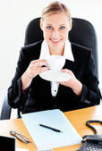 Radiant caucasian businesswoman holding a coffee sitting at her — Stock Photo