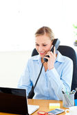 Ambitious businesswoman talking on phone using her laptop — Stock Photo
