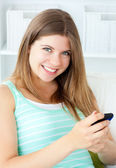 Smiling young woman texting on her cellphone in the living-room — Stock Photo