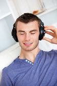 Relaxed young man listening to music with headphones in the livi — Stock Photo