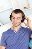 Handsome young man listening to music with headphones in the liv — 图库照片
