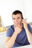 Handsome young man talkng on phone and smiling at the camera — Stock Photo