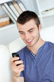 Charming young man sending a text and smiling in the living-room — Stock Photo