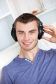 Bright young man listening to music sitting on the couch in the — Stock Photo