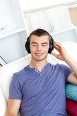 Relaxed young man listening to music sitting on the couch in the — Stock Photo