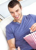 Positive caucasian man holding a remote and eating popcorn in th — Stock Photo