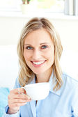 Captivating businesswoman holding a cup sitting on a sofa — Stock Photo