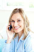 Cheerful businesswoman using her cellphone at home — Stock Photo