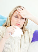 Ill woman holding a tissue sitting on a sofa — Stock Photo