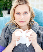 Diseased woman using a tissue sitting on a sofa — Stock Photo