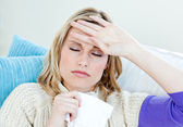 Sick woman with headache lying on the sofa in the living-room — Stock Photo